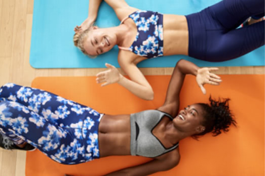 two women lay on yoga mats