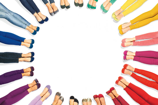 women with different color pants and shoes lay in circle to create a color wheel